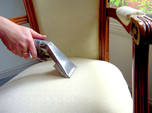 person cleaning upholstery chair